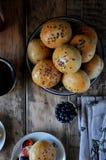 De eigengemaakte broodjes met de zaden van de lijnzaadzonnebloem voor ontbijt met boter en bosbes blokkeren royalty-vrije stock foto's