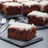 De eigengemaakte brownie met kokosnotenvlokken, Zweeds dessert Karleksmums, besnoeiing in vierkante porties, op plaat en koelrek, stock fotografie