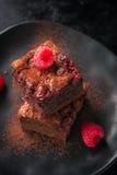 De eigengemaakte cakes van chocolade zoete brownies met kers en frambozen op een donkere achtergrond Stock Foto's