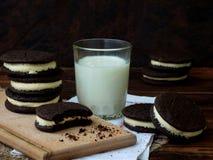De eigengemaakte chocoladekoekjes met witte heemst romen en glas melk op donkere achtergrond af Royalty-vrije Stock Afbeeldingen