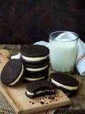 De eigengemaakte chocoladekoekjes met witte heemst romen en glas melk op donkere achtergrond af Selectieve nadruk Royalty-vrije Stock Afbeelding