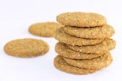 De eigengemaakte die zandkoekkoekjes van havermeel worden gemaakt worden gestapeld op een witte lijstachtergrond Het concept van  stock afbeelding