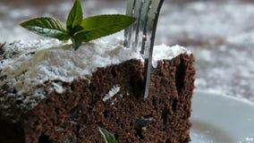 De eigengemaakte gebakken die cake van de chocoladebrownie met gepoederde suiker op een witte die plaat wordt gedempt met munt wo stock video