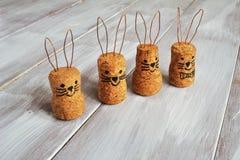 De eigengemaakte grappige ongehoorzame die Pasen-hazen worden gemaakt van kurken en de metaalkantoorbehoeften op lichte houten ac stock afbeelding