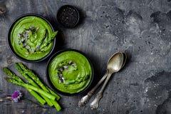 De eigengemaakte groene die de roomsoep van de de lenteasperge met zwarte sesamzaden en eetbaar bieslook wordt verfraaid bloeit stock afbeeldingen