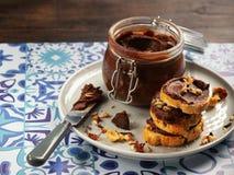 De eigengemaakte hazelnootroom in kom met hazelnootnoten en de plakken van toost met chocolade romen op houten achtergrond met ex stock afbeeldingen