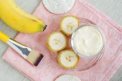 De eigengemaakte het maskerroom van het banaangezicht in de kleine glaskruik en het schoonheidsmiddel borstelen DIY-schoonheidsbe royalty-vrije stock afbeeldingen