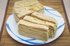 De eigengemaakte honingscake ligt op een plaat op een bamboeservet Close-up, selectieve nadruk stock foto's