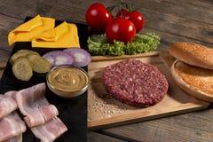 De eigengemaakte kaas van cheeseburger verse ingrediënten, broodje, zoutte komkommer, rundvleespasteitjes, bacon Royalty-vrije Stock Foto