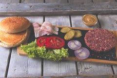 De eigengemaakte kaas van cheeseburger verse ingrediënten, broodje, zoutte komkommer, rundvleespasteitjes, bacon Royalty-vrije Stock Afbeeldingen
