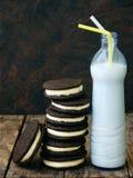 De eigengemaakte Oreo-chocoladekoekjes met witte heemst romen en botle van melk op donkere achtergrond af Stock Afbeeldingen