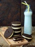 De eigengemaakte Oreo-chocoladekoekjes met witte heemst romen en botle van melk op donkere achtergrond af Royalty-vrije Stock Afbeelding