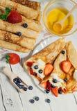 De eigengemaakte pannekoeken met wipped room en verse bessen stock foto