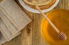 De eigengemaakte pannekoeken van het honingsbrood op een windwaartse houten achtergrond Stock Afbeeldingen