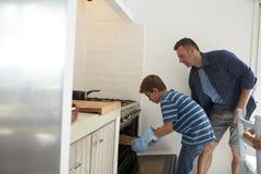 De Eigengemaakte Pizza van vaderand son baking in Oven royalty-vrije stock afbeelding