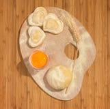 De eigengemaakte ravioli in de vorm van hart schikte met een oor van tarwe op een schilderspalet Stock Afbeelding