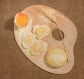 De eigengemaakte ravioli in de vorm van hart schikte met een oor van tarwe op een schilderspalet Royalty-vrije Stock Afbeeldingen
