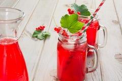 De eigengemaakte rode aalbeslimonade in een metselaarkruik en versiert van bessentak op ligth houten lijst Stock Fotografie