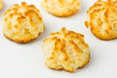 De eigengemaakte verse heerlijke koekjes van kokosnotenmakarons met gouden korst op witte keukenlijst Het baksel van het vakantie stock afbeelding
