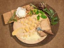 De eigengemaakte verse ravioli met prosciutto, okkernoten, spruitjes, artisjok en aromatische kruiden paste op een rustiek rond b Royalty-vrije Stock Foto