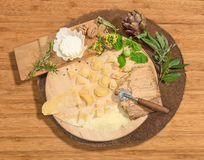 De eigengemaakte verse ravioli met prosciutto, okkernoten, spruitjes, artisjok en aromatische kruiden paste op een rustiek rond b Stock Foto