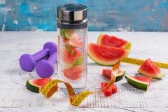 De eigengemaakte watermeloen detox goot water, domoren en het meten van band op houten achtergrond Royalty-vrije Stock Fotografie