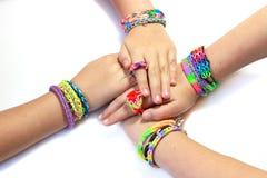 De elastische en kleurrijke armband van het regenboogweefgetouw op handen Royalty-vrije Stock Afbeeldingen