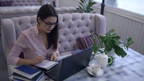 De ELearningstechnologie, glimlachend meisje met pen schrijft nota's in notitieboekjezitting bij lijst met laptop in koffie stock videobeelden