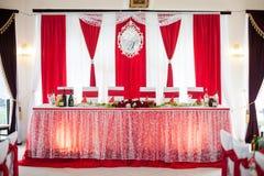 De elegant gerichte zaal van de huwelijksontvangst met rode linten op Lux Stock Foto's