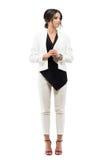 De elegante bedrijfsvrouw in kostuum die zich in formele houding met handen bevinden clasped weg het kijken royalty-vrije stock afbeelding