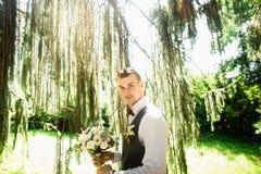 De elegante bruidegom is bereid om zijn bruid dichtbij de aard te ontmoeten stock afbeeldingen