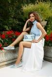 De elegante, elegante en modieuze jonge dame met make-up en kapsel stelt dichtbij het mooie herenhuis stock foto's