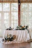 De elegante huwelijkslijst in de stijl van wijnoogst en plattelander verfraaide met bloemen, wit kant, tafelkleed en kaarsen royalty-vrije stock fotografie