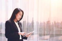 De elegante jonge bedrijfsvrouw die tablet gebruiken door het venster voor ontspant, bekijkend vaag het scherm en Bedrijfsdistric Stock Foto
