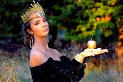 De elegante jonge vrouw kleedde zich als koningin Stock Foto's