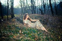 De elegante jonge vrouw zit op grond in bos royalty-vrije stock afbeelding
