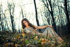 De elegante jonge vrouw zit op grond in bos royalty-vrije stock foto's