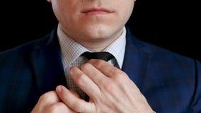 De elegante mannelijke zakenman in een wit overhemd en een kostuum bindt en maakt zijn band recht stock video