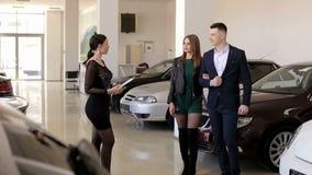 De elegante meisjesverkoper in een zwarte kleding die aan jongelui spreken koppelt in de autoshow stock videobeelden