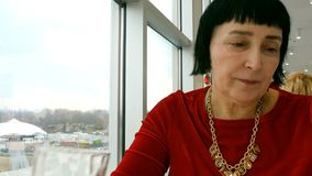De elegante oude vrouw, het Kaukasische behoren tot een bepaald ras, drinkt water van transparant glas stock video