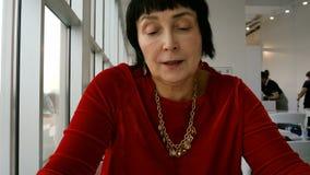 De elegante oude vrouw, het Kaukasische behoren tot een bepaald ras, leest menu stock video
