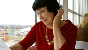 De elegante oude vrouw, het Kaukasische behoren tot een bepaald ras, leest menu in restaurant of koffie stock video