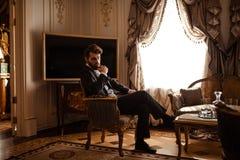 De elegante rijke zakenman in formeel zwart kostuum, zit op stoel in koninklijke ruimte, voelt ontspannen, heeft ernstige nadenke stock foto's