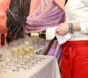 De elegante serveerster giet champagne in groep glazen stock fotografie