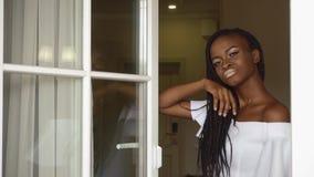 De elegante sexy Afrikaanse Amerikaanse dame kijkt zorgvuldig door het venster op de de flatsachtergrond van het luxehotel stock video