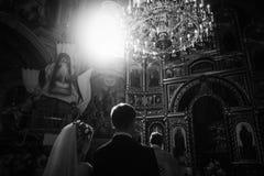 De elegante sluier van de bruidholding en het stellen met bruidegom in zonlicht und stock foto