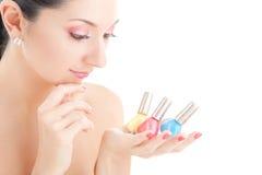 De elegante vrouw kiest de kleur van nagellak Stock Afbeeldingen