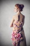 De elegante vrouw kleedde zich met bloemen stock foto's