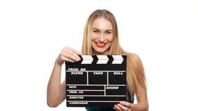 De elegante vrouw met sexy rode lippen gaat, gebruikend kleppenraad en glimlachend, op wit stock videobeelden