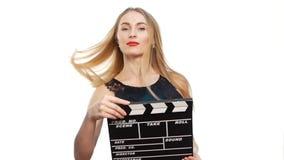 De elegante vrouw met sexy rode lippen gaat, gebruikend kleppenraad en glimlachend, op witte, langzame motie stock videobeelden